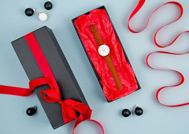 Relógio de mão de mulher embalado na caixa de presente preta com fita vermelha
