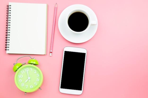 Relógio de notebook verde café preto telefone móvel no fundo rosa