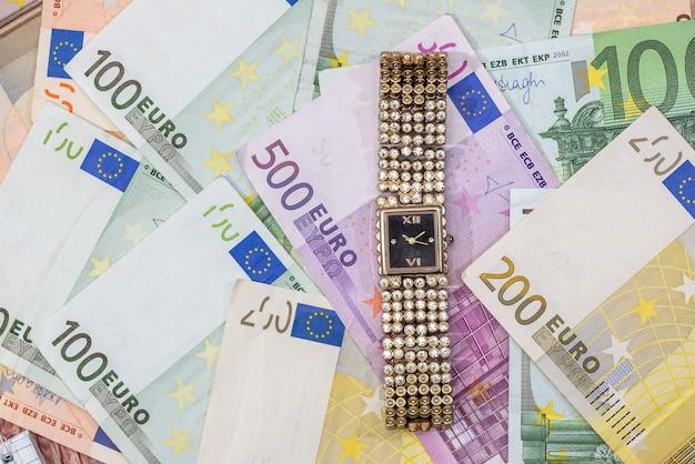 Relógio de ouro da mulher nas notas de euros. fechar-se.