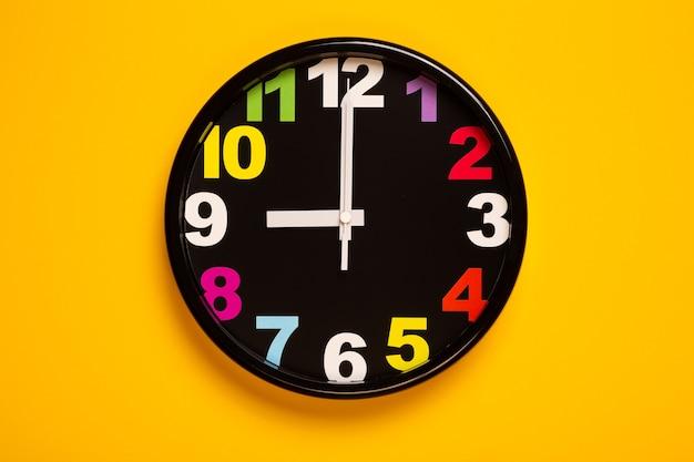 Relógio de parede colorido mostra nove horas
