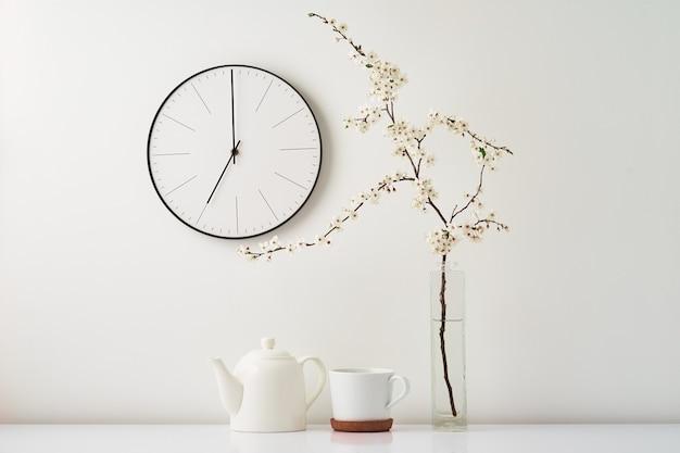 Relógio de parede florescendo ramo de cereja e xícara de chá no fundo branco vista frontal decoração interior hora do chá