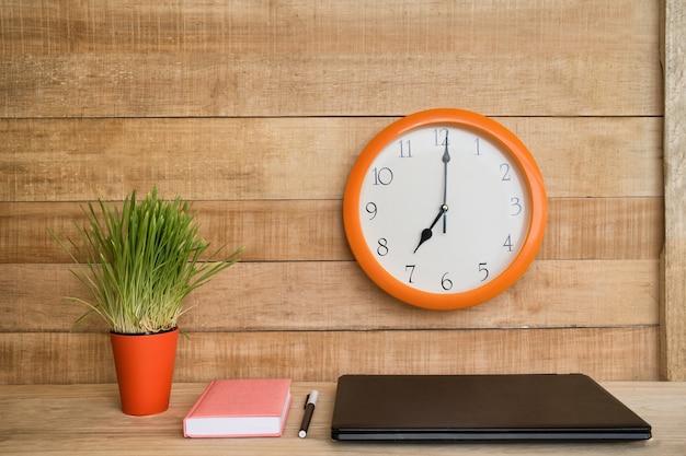 Relógio de parede, laptop, caderno e caneta