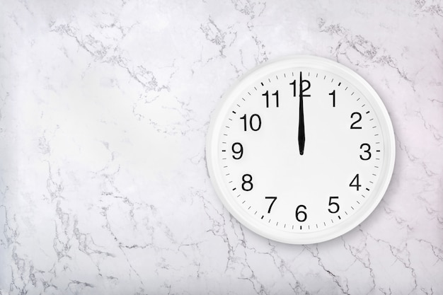Relógio de parede redondo branco sobre fundo branco de mármore natural. meio dia