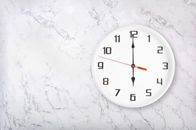 Relógio de parede redondo branco sobre fundo branco de mármore natural. seis horas