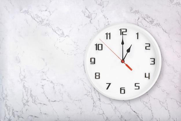 Relógio de parede redondo branco sobre fundo branco de mármore natural. uma hora
