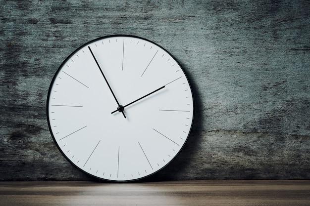Relógio de parede redondo clássico em um fundo de madeira com espaço de cópia
