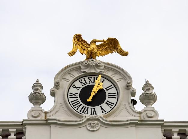 Relógio de pedra com uma águia dourada em cima de um edifício do palácio de schönbrunn.