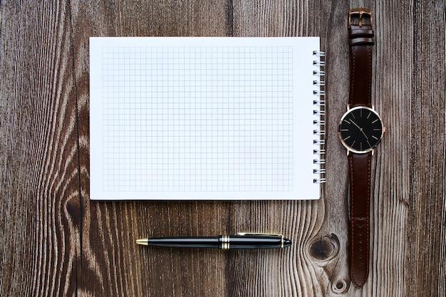 Relógio de pulso, caderno em branco, caneta na vista superior do plano de fundo de madeira.