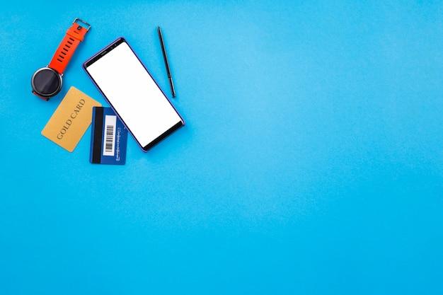 Relógio de pulso; celular; e cartão de crédito na superfície azul para compras on-line