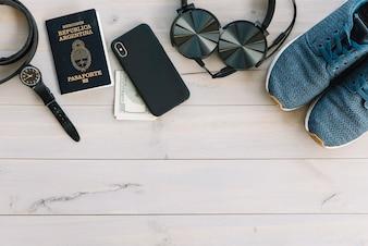 Relógio de pulso; celular; moeda; fone de ouvido e sapatos na mesa de madeira