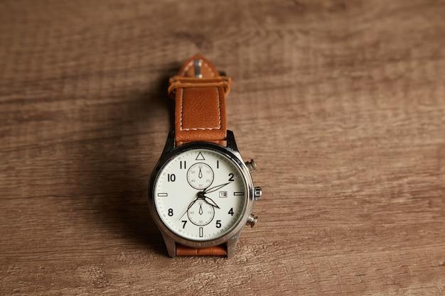 Relógio de pulso com pulseira de couro em mesa de madeira