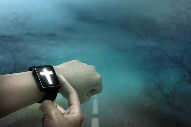 Relógio de pulso digital com cruz cristã na mão humana e fundo noturno