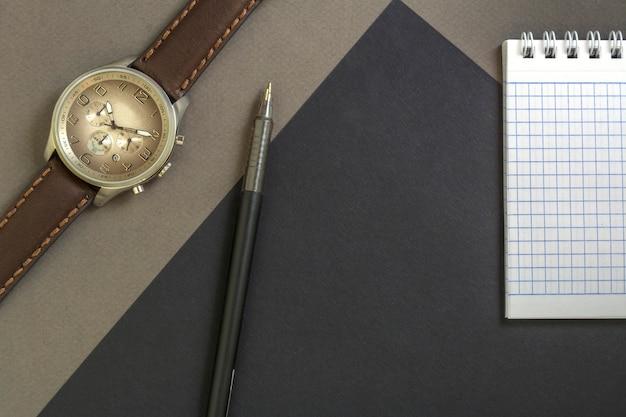 Relógio de pulso dos homens bonitos no fundo cinzento. bloco de notas e caneta preta sobre fundo preto