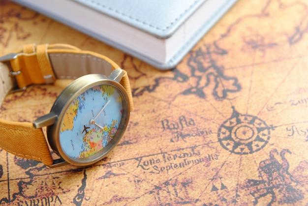 Relógio de pulso e caderno no mapa mundial