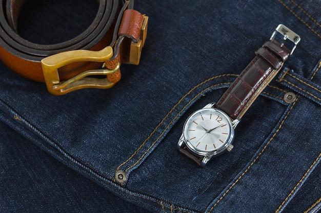 Relógio de pulso e cinto de couro em jeans