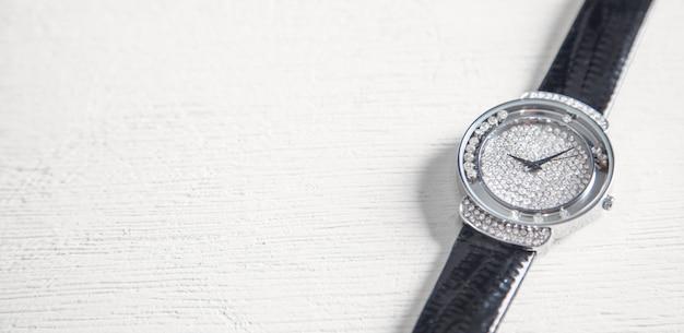 Relógio de pulso feminino na mesa branca.