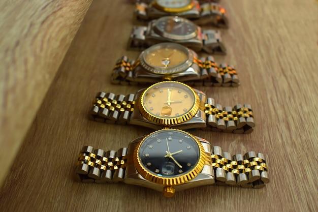 Relógio de pulso fino, colocado sobre um piso de vidro brilhante