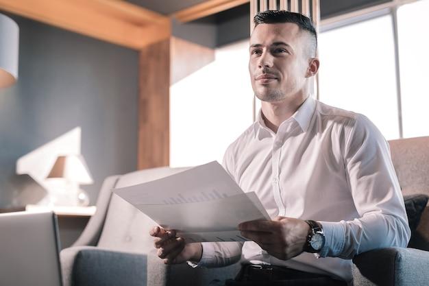 Relógio de pulso. jovem e bonito diretor financeiro de cabelos escuros usando um belo relógio de mão enquanto está sentado no sofá