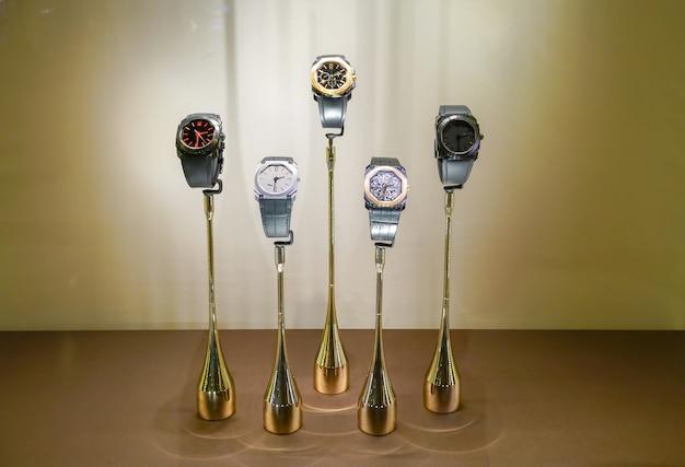 Relógio de pulso luxuoso moderno no suporte moderno do ouro contra a luz - exposição marrom do fundo.