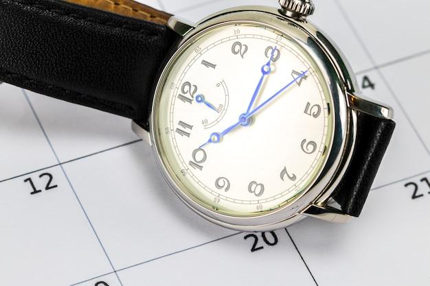 Relógio de pulso masculino e calendário. conceito de data e hora.