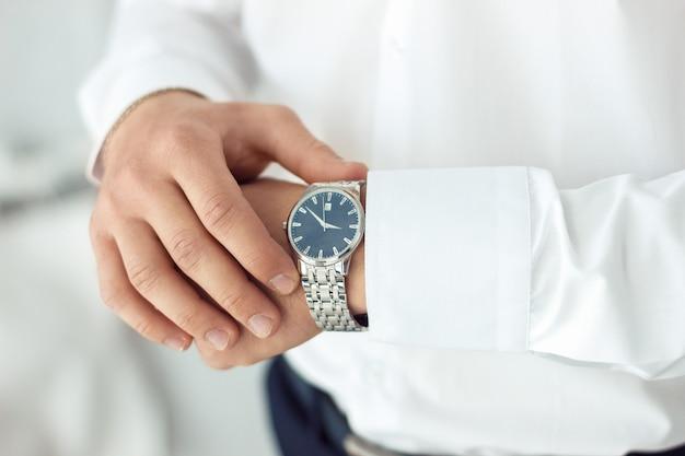Relógio de pulso masculino, o homem está assistindo o tempo. relógio de empresário, empresário, verificando o tempo em seu relógio de pulso.