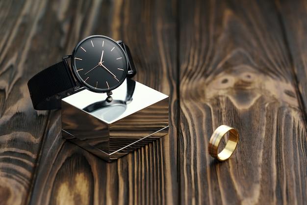 Relógio de pulso moderno preto no cubo cromado com anel de ouro sobre fundo de madeira