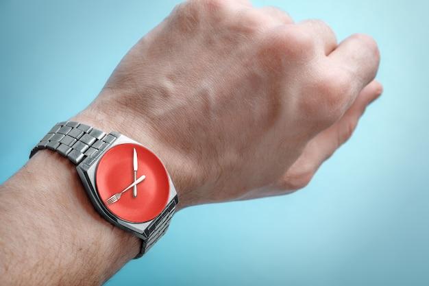 Relógio de pulso na mão do homem. prato, faca e garfo na face do relógio. conceito de jejum intermitente, hora do almoço