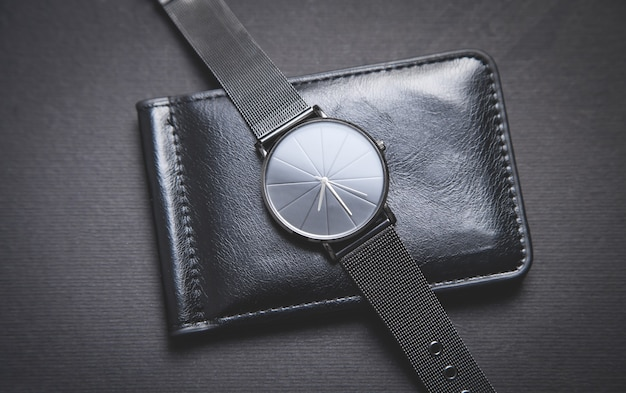 Relógio de pulso preto e carteira de couro preta no fundo preto