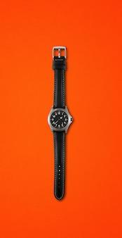 Relógio de pulso preto isolado em fundo vermelho