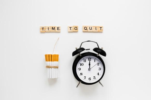 Relógio de vista superior com cigarros e palavras