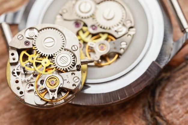 Relógio desmontado em mesa de madeira, vista de cima