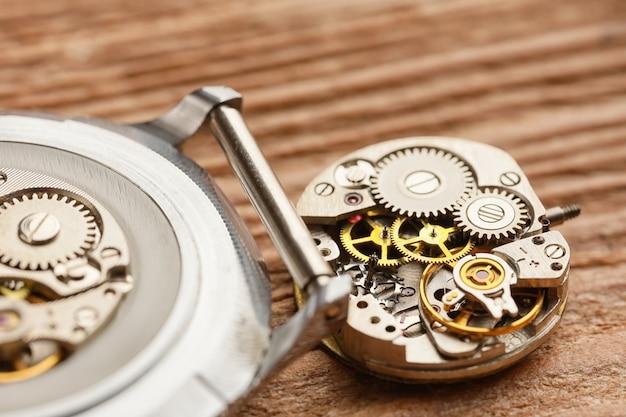 Relógio desmontado na mesa de madeira, close-up