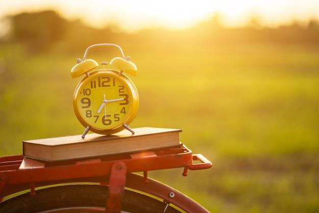 Relógio despertador amarelo e livro colocar na bicicleta clássica estilo vermelho japão