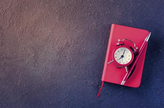 Relógio despertador, bloco de notas e caneta em fundo escuro