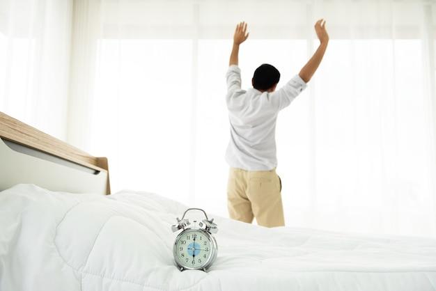 Relógio despertador com as costas do homem asiático esticar-se no fundo do quarto.