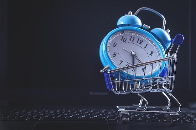 Relógio despertador com carrinho de compras no teclado do computador.