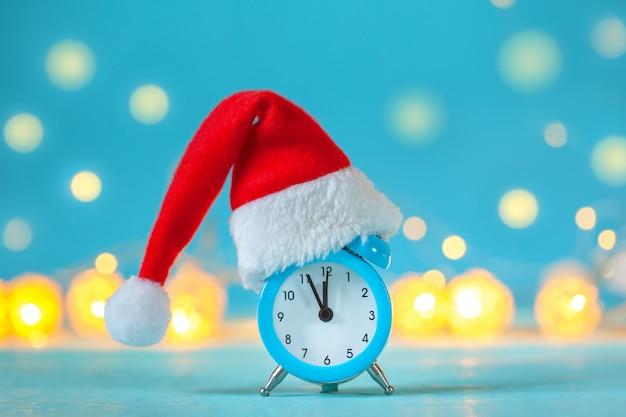 Relógio despertador com chapéu de natal papai noel. hora do natal. cartão com espaço de cópia de texto.