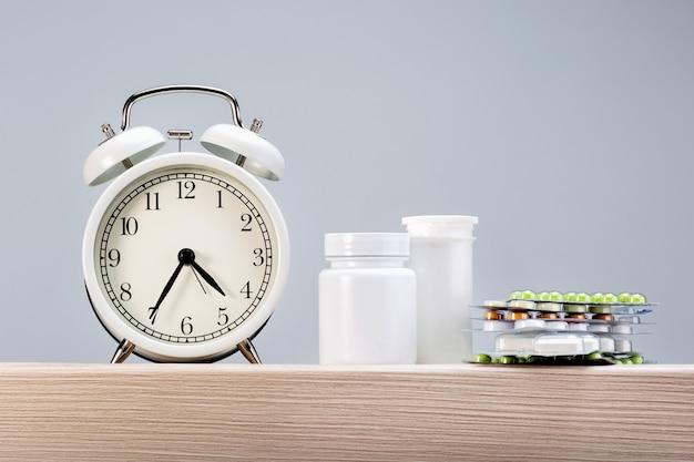 Relógio despertador com comprimidos em cima da mesa contra um fundo cinza com espaço de cópia.