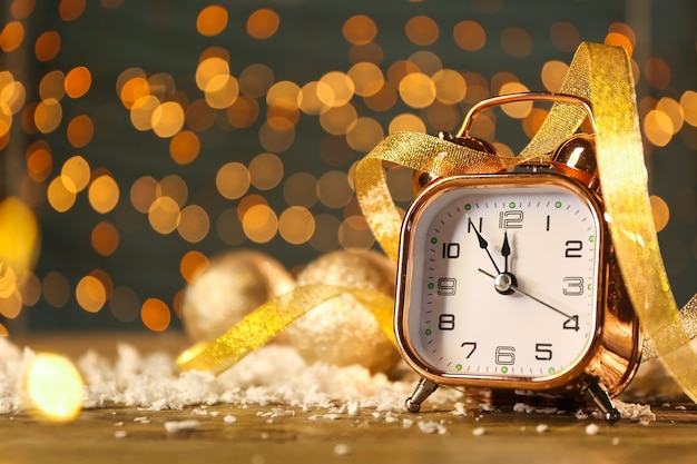 Relógio despertador com fita e neve na mesa contra luzes desfocadas.