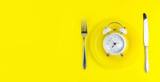 Relógio despertador com garfo e faca no fundo amarelo claro. hora de comer, conceito de café da manhã, hora de almoço e jantar. copiar espaço, banner