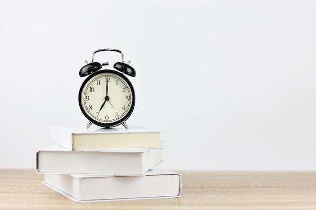 Relógio despertador com livros na mesa de madeira