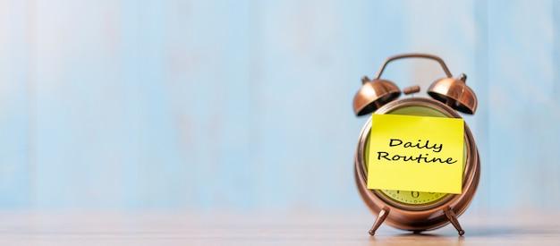 Relógio despertador com papel de nota de rotina diária na mesa de madeira