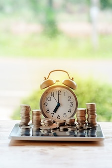 Relógio despertador com pilhas de moedas no fundo da natureza