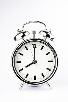 Relógio despertador de metal no fundo branco