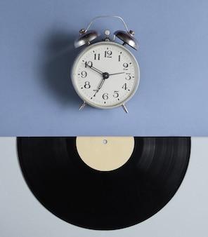 Relógio despertador, disco de vinil em fundo cinza azul. estilo retrô. vista do topo