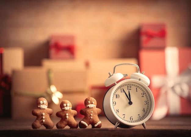 Relógio despertador e biscoitos com presentes de natal no fundo