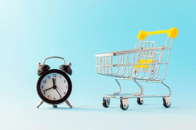 Relógio despertador e carrinho de compras em miniatura sobre fundo azul claro