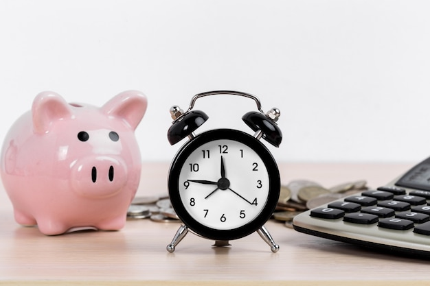 Relógio despertador e cofrinho com moedas e calculadora