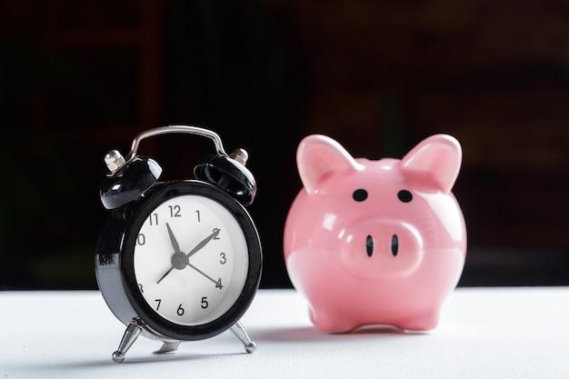 Relógio despertador e cofrinho conceito para poupar tempo