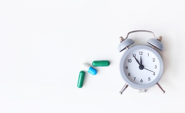 Relógio despertador e comprimidos médicos em fundo branco
